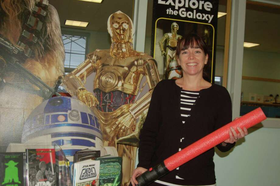 Deirdre Sullivan, head of childrenís services in Greenwich Library, holds a lightsaber made out of a pool noodle. A special Star Wars craft program is set for Dec. 12. Photo: Ken Borsuk / Hearst Connecticut Media / Greenwich Time