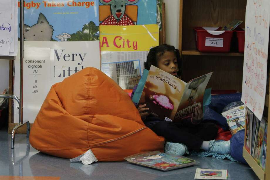 First-grader Kylee Dennings reads on a bean bag in the classroom library at Mading Elementary. Photo: Steve Gonzales, Staff / © 2015 Houston Chronicle