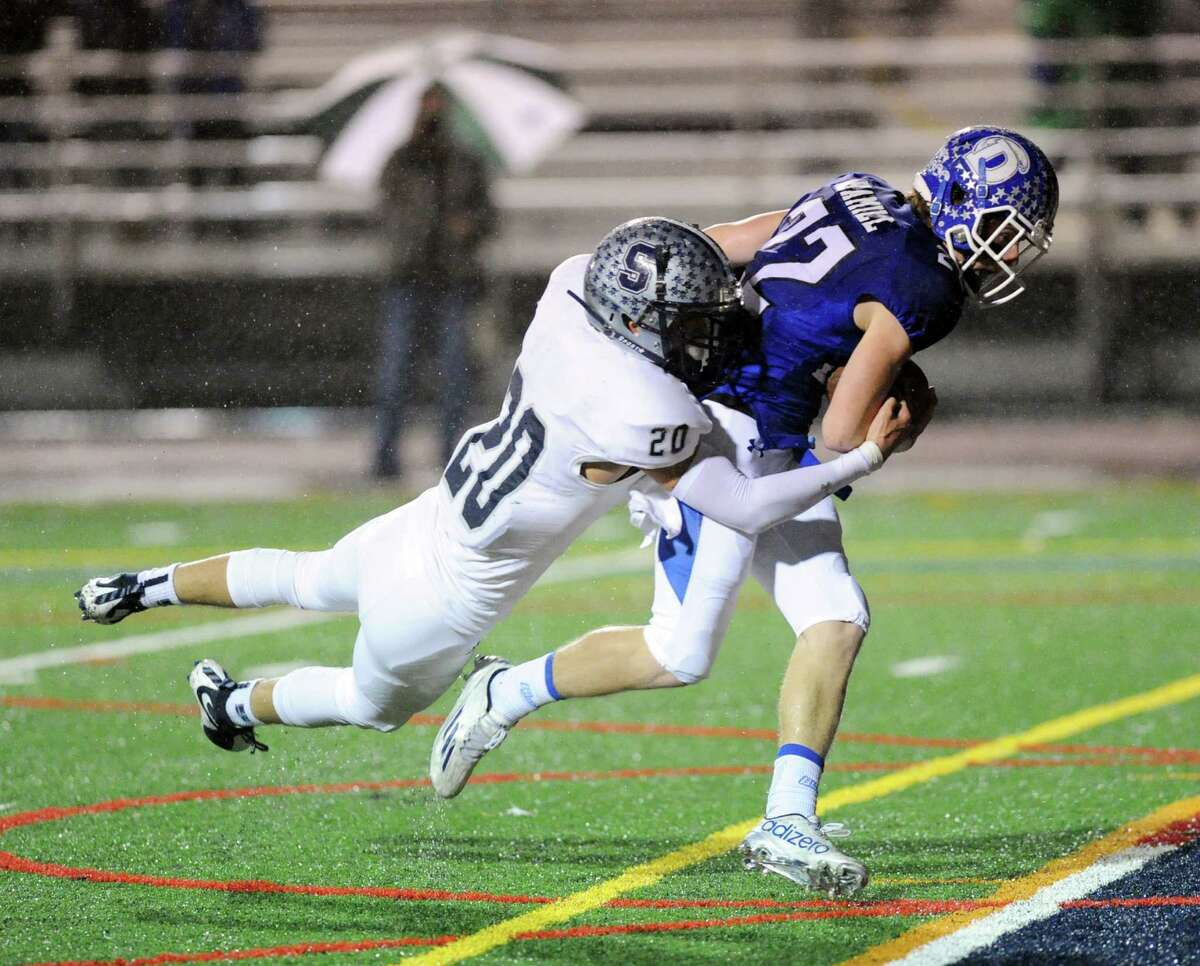 Hudson Hamill (#22) of Darien at right, drags Staples defender Elliott Poullley (#20) into the endzone to score on a pass from quarterback Tim Graham during the first quarter of the Class LL football playoff game bewteen Staples High School and Darien High School at Brien McMahon High School in Norwalk, Conn., Tuesday night, Dec. 1, 2015.