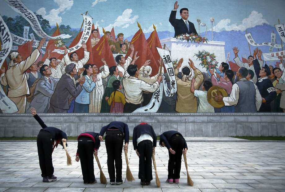 North Korean school girls holding brooms bow to pay their respects toward a mural which shows the late North Korean leader Kim Il Sung delivering a speech, before sweeping the area surrounding this mural on Tuesday, Dec. 1, 2015, in Pyongyang, North Korea. Photo: Wong Maye-E, Associated Press
