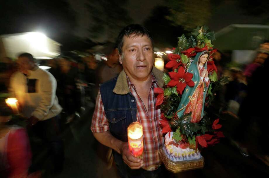 Justino Hernandez carries a Virgin of Guadalupe statue during a procession with Danza los Gorriones last month in Houston. Photo: Melissa Phillip, Staff / © 2015 Houston Chronicle