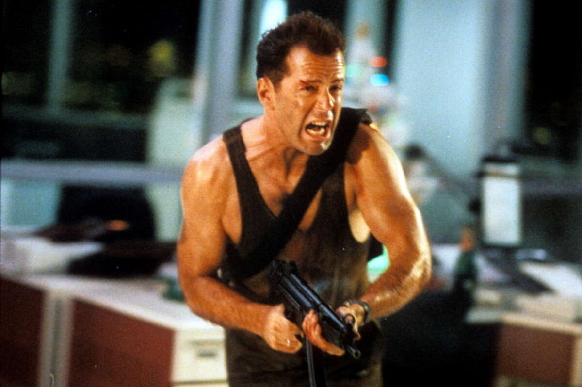 Bruce Willis running with automatic weapon in a scene from the film 'Die Hard', 1988. Not the usual holiday movie, but it has an effective holiday angle.