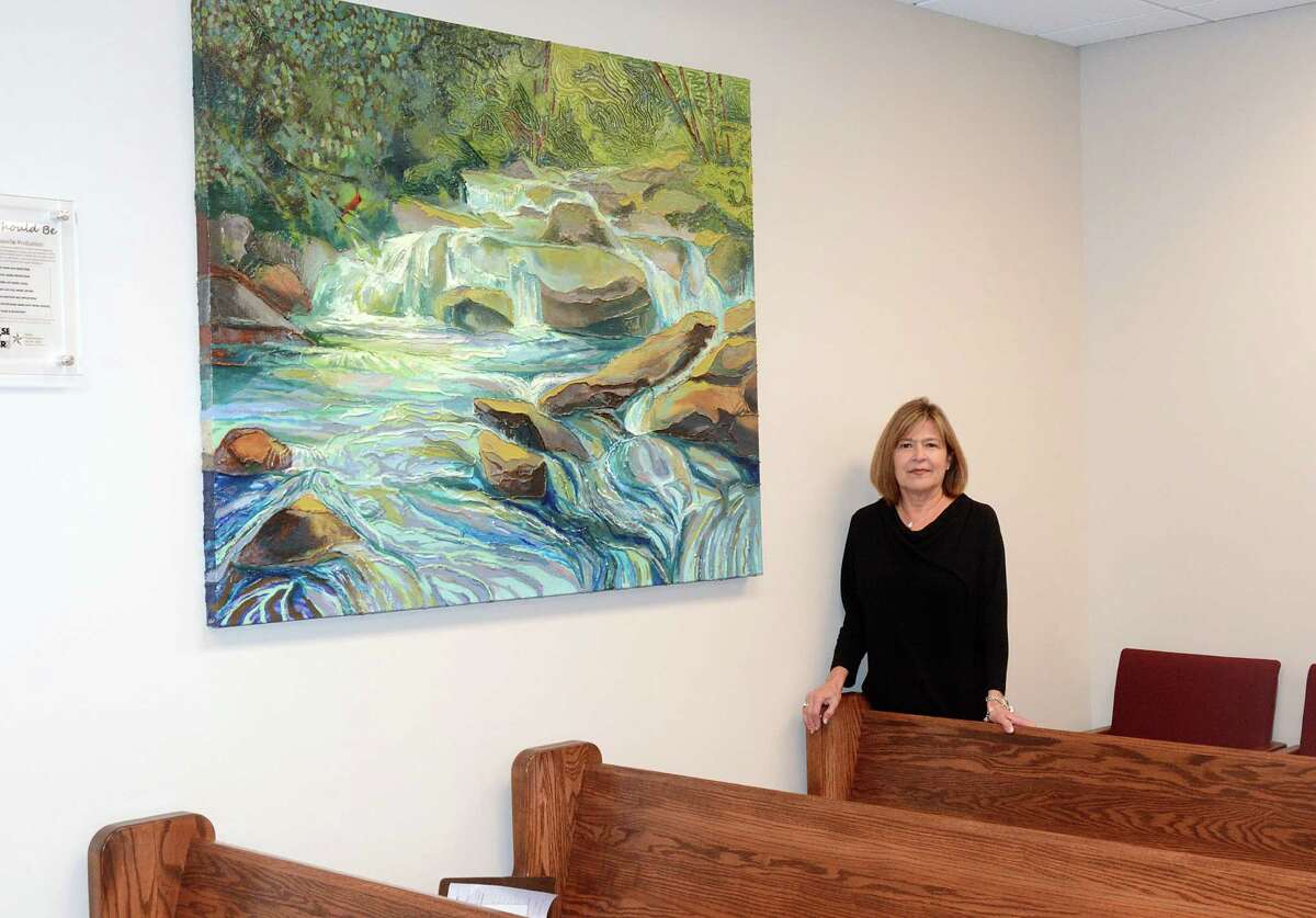 Judge Mary Ann Turner stands by a painting painted by juveniles at the MoCo Juvenile Justice Center in her County Court at Law #4 courtroom, 210 W. Davis Street in downtown Conroe. Photograph by David Hopper