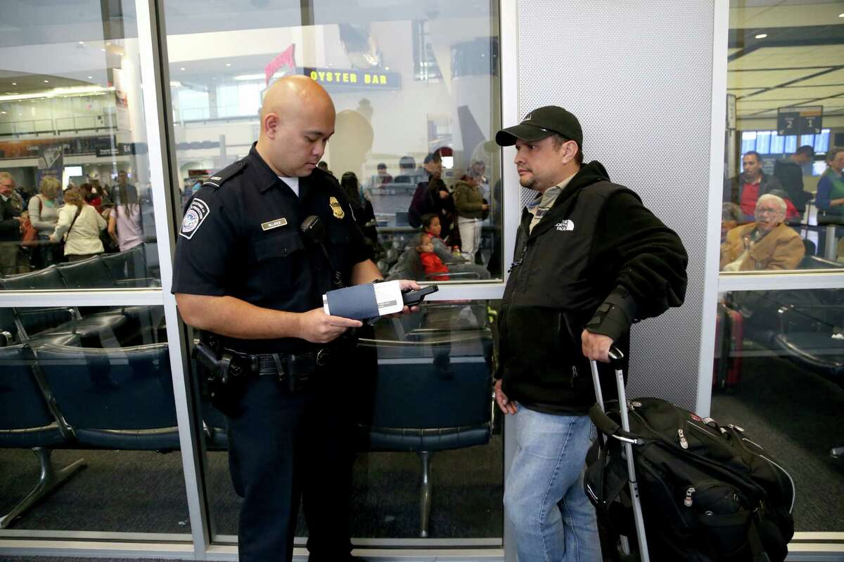 U.S. Customs and Border Protection officer J. Vallarde, shown with passenger Oscar Guerrero, of Guatemala, test a handheld mobile device to collect biometric exit data, two finger prints, from a limited number of foreign national air travelers departing from the U.S. at Bush Intercontinental Airport Tuesday, Dec. 1, 2015, in Houston, Texas. ( Gary Coronado / Houston Chronicle )