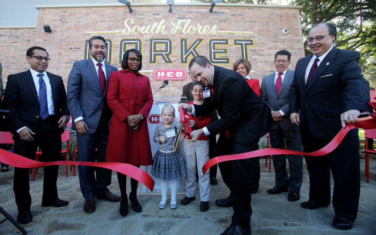 Nick George (right, center, holding scissors), store director at the new South Flores H-E-B Market store, cuts the ribbon at opening ceremonies with his daughter Stella,3, (center) and son Sutton,6. The new South Flores H-E-B Market store at the corner of Cesar Chavez and South Flores in downtown San Antonio, Texas opened at 7:00 a.m. Wednesday December 2, 2015. Standing next to George's daughter (wearing red coat) is San Antonio mayor Ivy Taylor.