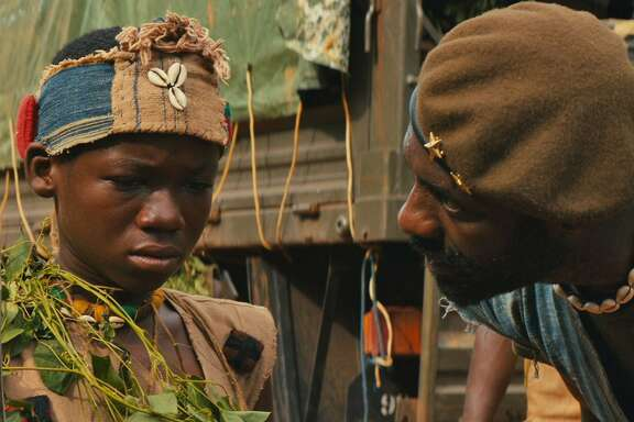 """Beasts Attah Elba  Total acting novice Abraham Attah (left, as """"Beasts of No Nation"""" protagonist Agu) has been honored by the Independent Spirit Awards with a nomination in the lead actor category. He was 11 when the film was shot. Costar Idris Elba (right, as the Commandant) was nominated in the supporting category. """"Beasts of No Nation"""" is available on Netflix. Photo courtesy of Netflix."""