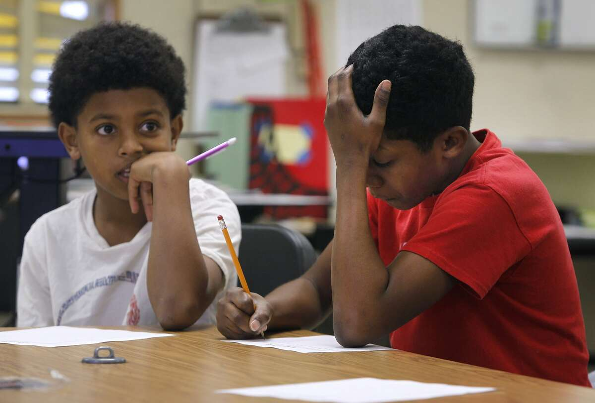 Jordon Chatmon (left) and Azriel Shakur work on a classroom exercise in a Manhood Development class for 6th grade boys at Montera Middle School in Oakland, Calif. on Wednesday, Dec. 2, 2015.