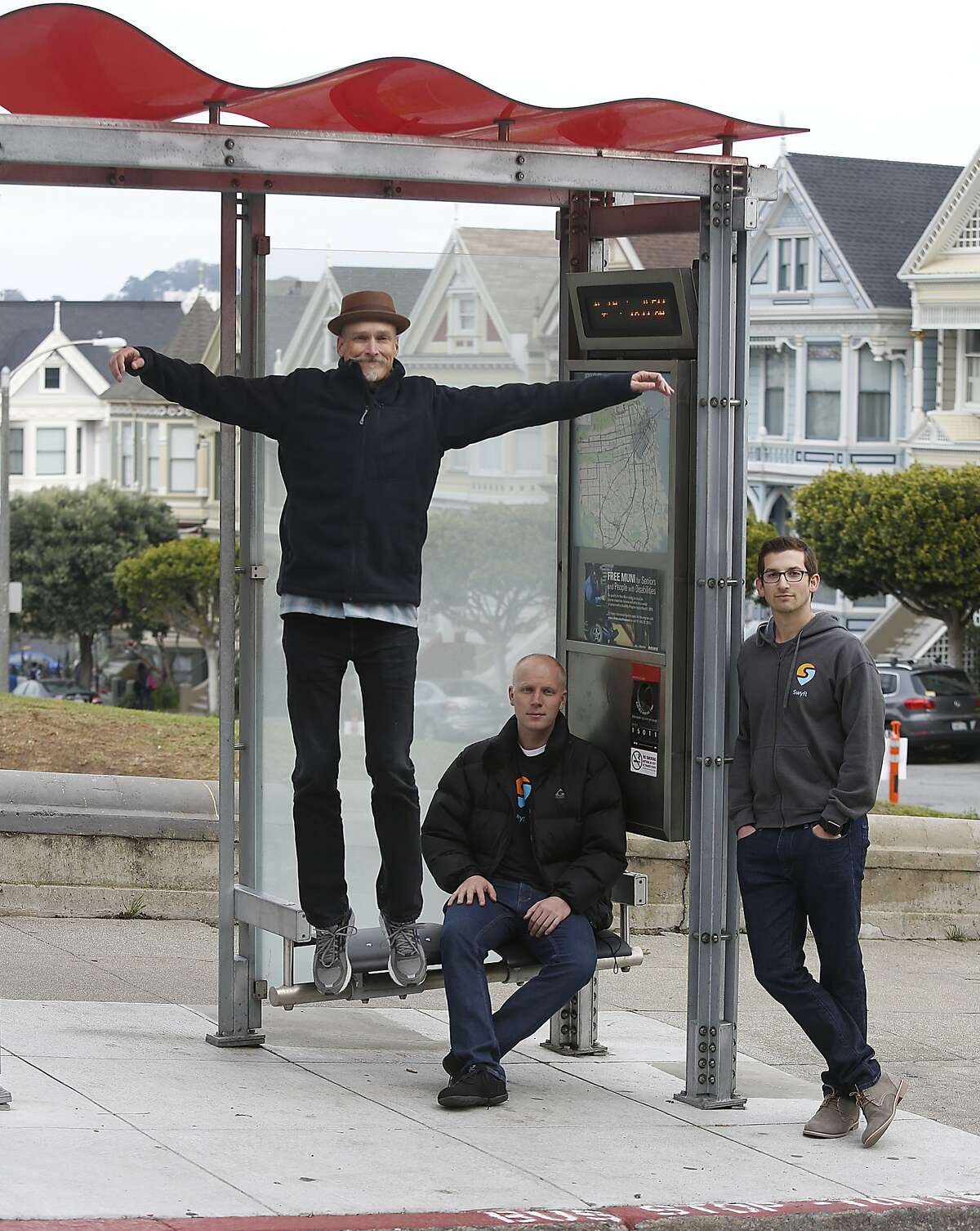 Swyft co-founders Michael Smith (left), Will Dayton (middle), and Jonny Simkin (right) at the bus stop next to Alamo park on Hayes St. in San Francisco, California, on Wednesday, December 2, 2015.
