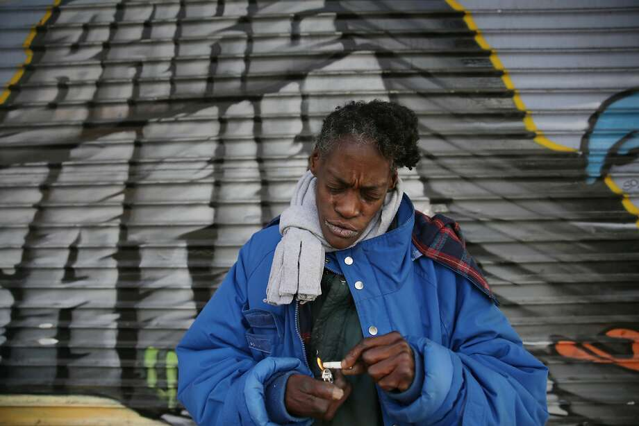 "Rosalyn Burton, 56, lights a cigarette butt as she stands on Mission Street across fro the Navigation Center on Wednesday, December 2,  2015 in San Francisco, Calif.  Burton says she has been homeless for 14 years and is hoping to get a spot at the Navigation Center but the waiting list was already filled when she visited. She says she is tired of shelters and needs her own place. ""It's too much. I'm tired of shelter hopping,"" she said. Photo: Lea Suzuki, The Chronicle"