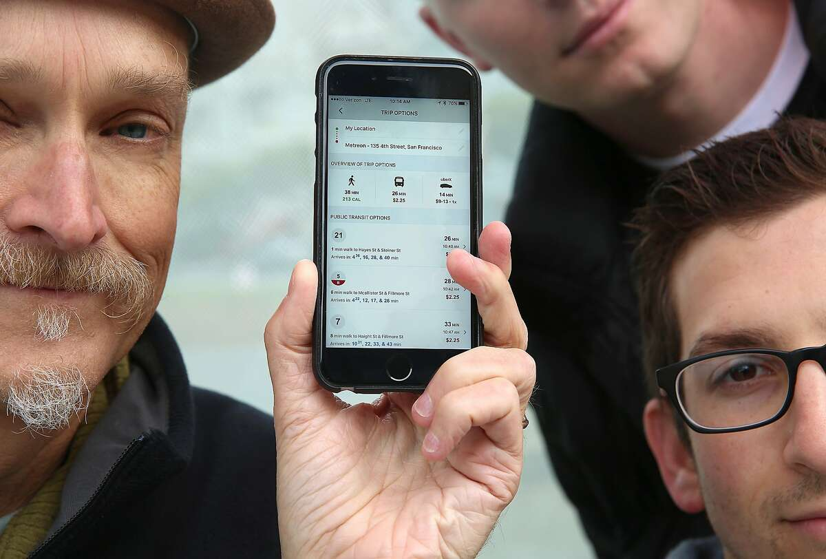 Swyft co-founders Michael Smith (left), Will Dayton (top), and Jonny Simkin (right) show their app at the bus stop next to Alamo park on Hayes St. in San Francisco, California, on Wednesday, December 2, 2015.