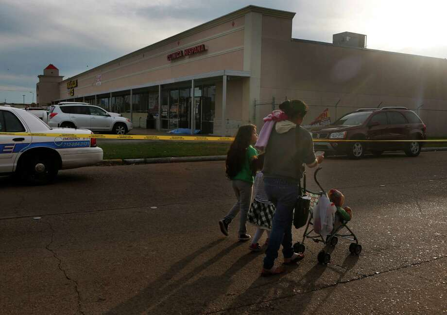 A family walks past the scene of a shooting outside the door of the Clinica Hispana at Fondern Road and Kings Gate Circle, Wednesday, Dec. 2, 2015, in Houston. Photo: Mark Mulligan, Houston Chronicle / © 2015 Houston Chronicle
