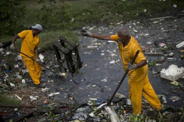 In this Nov. 5, 2015 photo, workers remove garbage collected by floating waste barriers in the Meriti River, which flows into Guanabara Bay in Rio de Janeiro, Brazil. A new round of testing by The Associated Press shows the city's Olympic waterways are as rife with pathogens far offshore as they are nearer land, where raw sewage flows into them from fetid rivers and storm drains. . (AP Photo/Silvia Izquierdo)