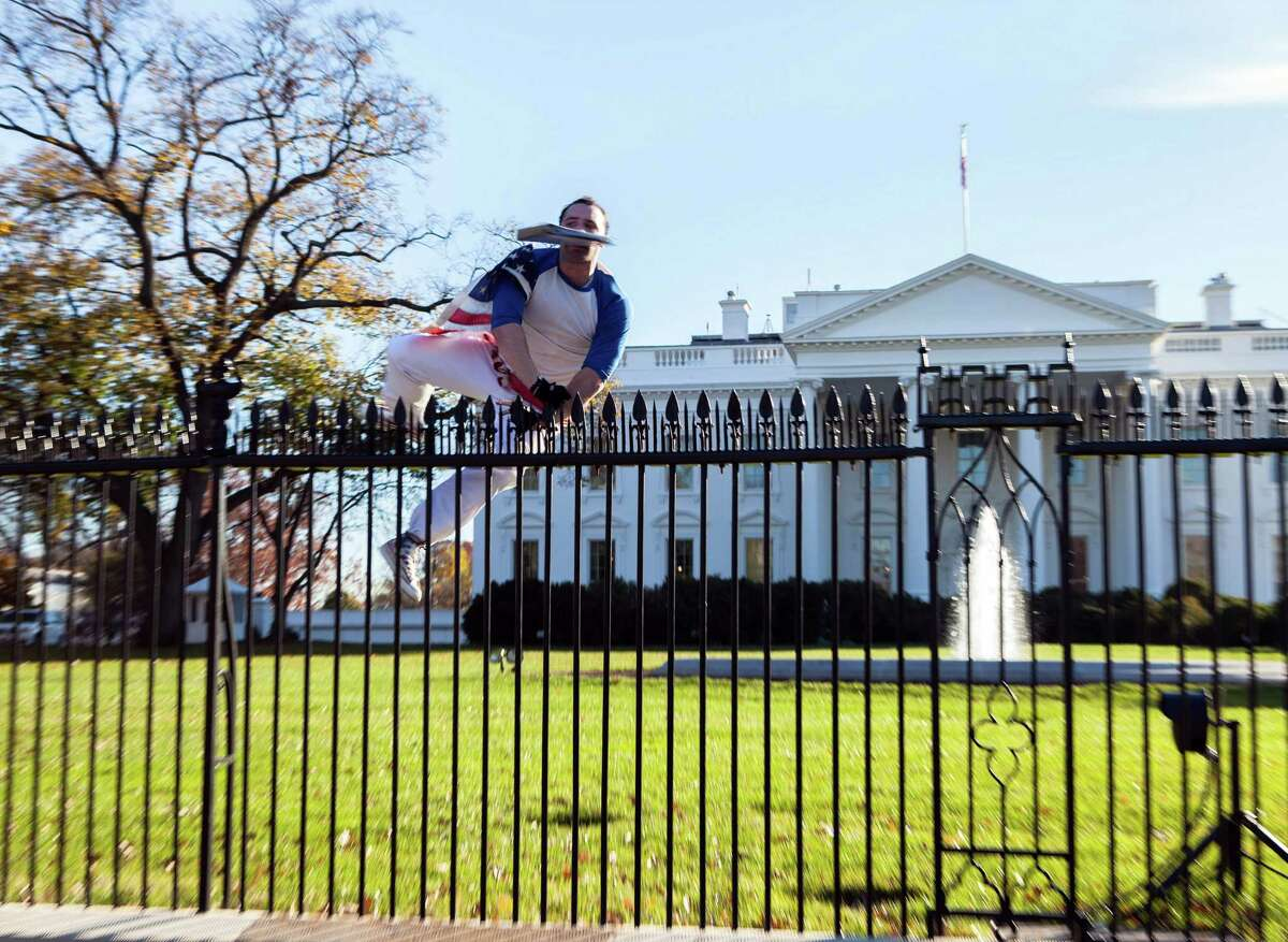 In this photo provided by Vanessa Pena, Joseph Caputo of Stamford jumps a fence at the White House on Thursday, Nov. 26.