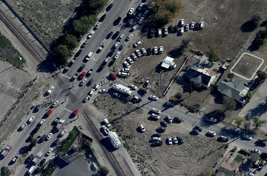 Police and emergency vehicles line Waterman Avenue in front of the Inland Regional Center in San Bernardino, Calif., scene of a mass shooting on Wednesday, Dec. 2, 2015.  As many as three gunmen believed to be wearing military-style gear opened fire Wednesday at the Southern California social services center. Authorities said the shooting rampage killed multiple people and wounded others. Photo: Luis Sinco, AP / Los Angeles Times