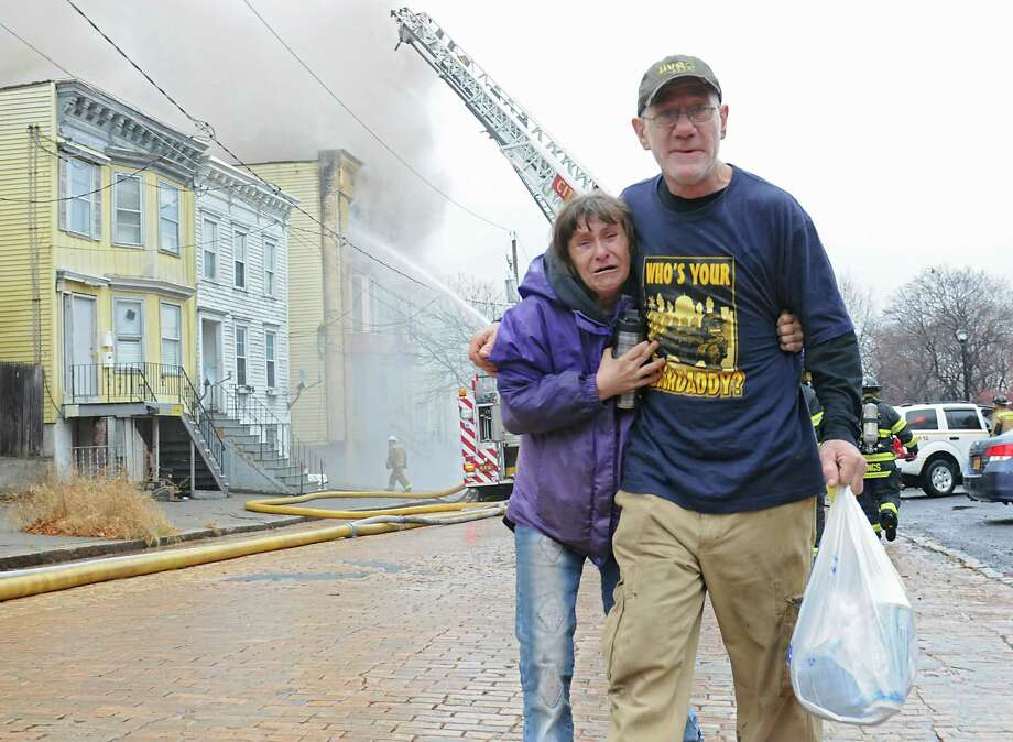 Anna Burbridge and James Blair walk away from their engulfed home on Park Ave. with a bag of belongings as firefighters fight a fire at three structures Wednesday Dec. 2, 2015 in Albany, N.Y. Burbridge and Blair were recently homeless until they moved into their apartment in the background. James said he had just made his first payment on the rent.  (Lori Van Buren / Times Union) Photo: Lori Van Buren