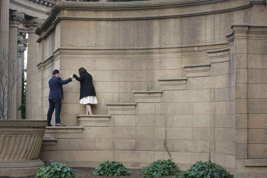 Gabriel Martinez (l to r) of San Jose leads Gabriela De La Torre of San Martin down steps on the rotunda at the Palace of Fine Arts after they posed for engagement photos on Wednesday, December 2,  2015 in San Francisco, Calif. Photo: Lea Suzuki, The Chronicle