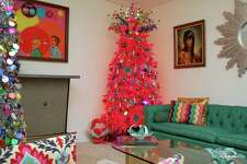 A hot pink Christmas tree from Treetopia (www.treetopia.com) decorates the Austin home of Jennifer Perkins, a member of Treetopia's design council. On the left is Treetopia's Tinkerbell silver tree adorned with colorful tinsel garland. Multiple trees in one room or throughout the home is a hot tree trend this year, Perkins said.