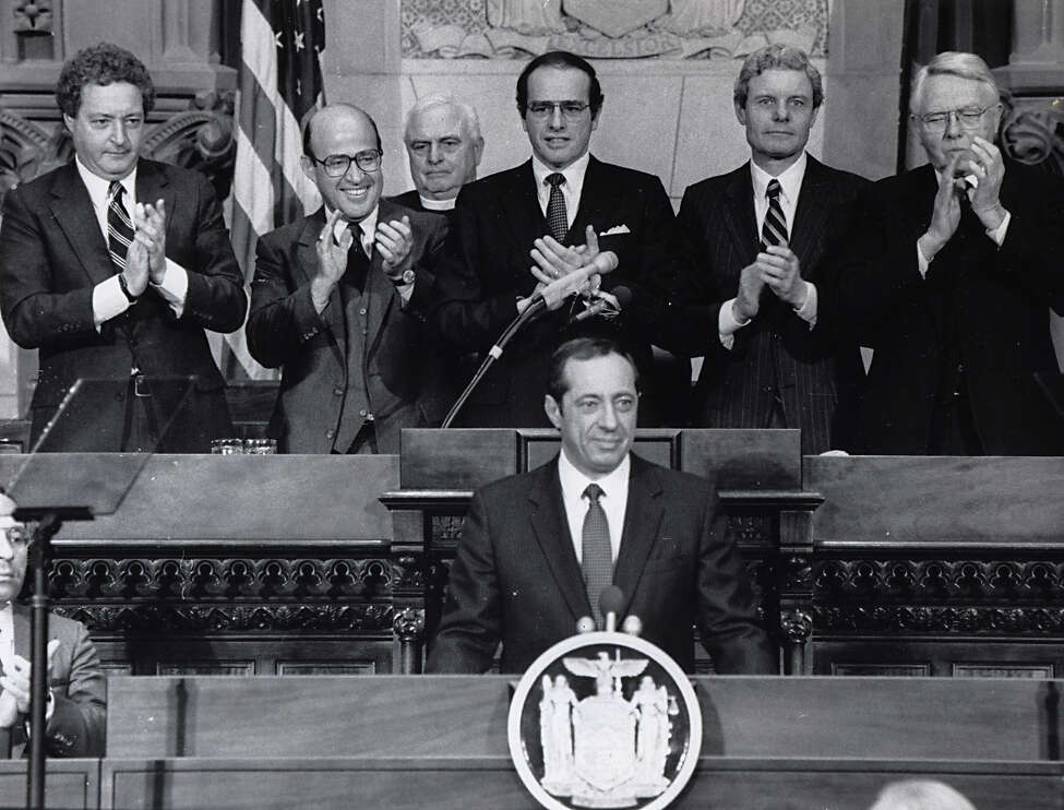 Times Union file photo of Gov. Mario Cuomo during the beginning of his state of the state address in Albany, N.Y. on January 4, 1989. Back row: from left, Assembly speaker Stanley Fink, Attorney General Robert Abrams, Assembly Chaplain Rev. Laman Brunner of St. Peters's Church, Lt. Gov. Alfred DelBello, Comptroller Ned Regan and Senate Majority Leader Warren Anderson.