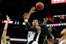 Spurs' Danny Green (14) makes a pass between the Milwaukee Bucks' Tyler Ennis (11) and O.J. Mayo (03) at the AT&T Center on Wednesday, Dec. 2, 2015.