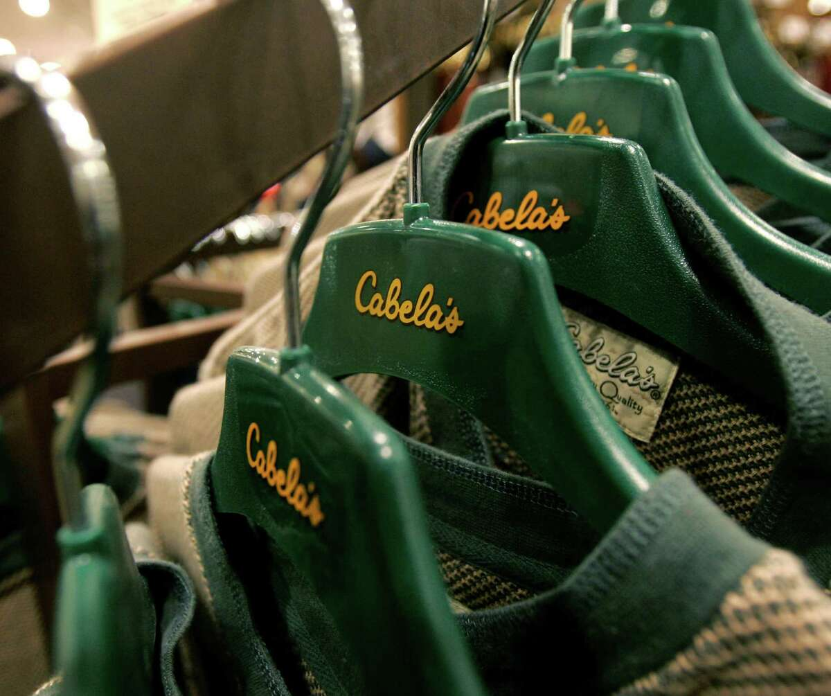 Shirts hang on hangers at the Cabela's store in Lacey, Wash. Cabela's says it may sell all or part of itself.