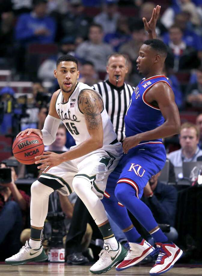 Michigan State guard Denzel Valentine, left, drives against Kansas forward Jamari Traylor during the first half of an NCAA college basketball game on Tuesday, Nov. 17, 2015 in Chicago. (AP Photo/Charles Rex Arbogast) Photo: Charles Rex Arbogast, STF / AP