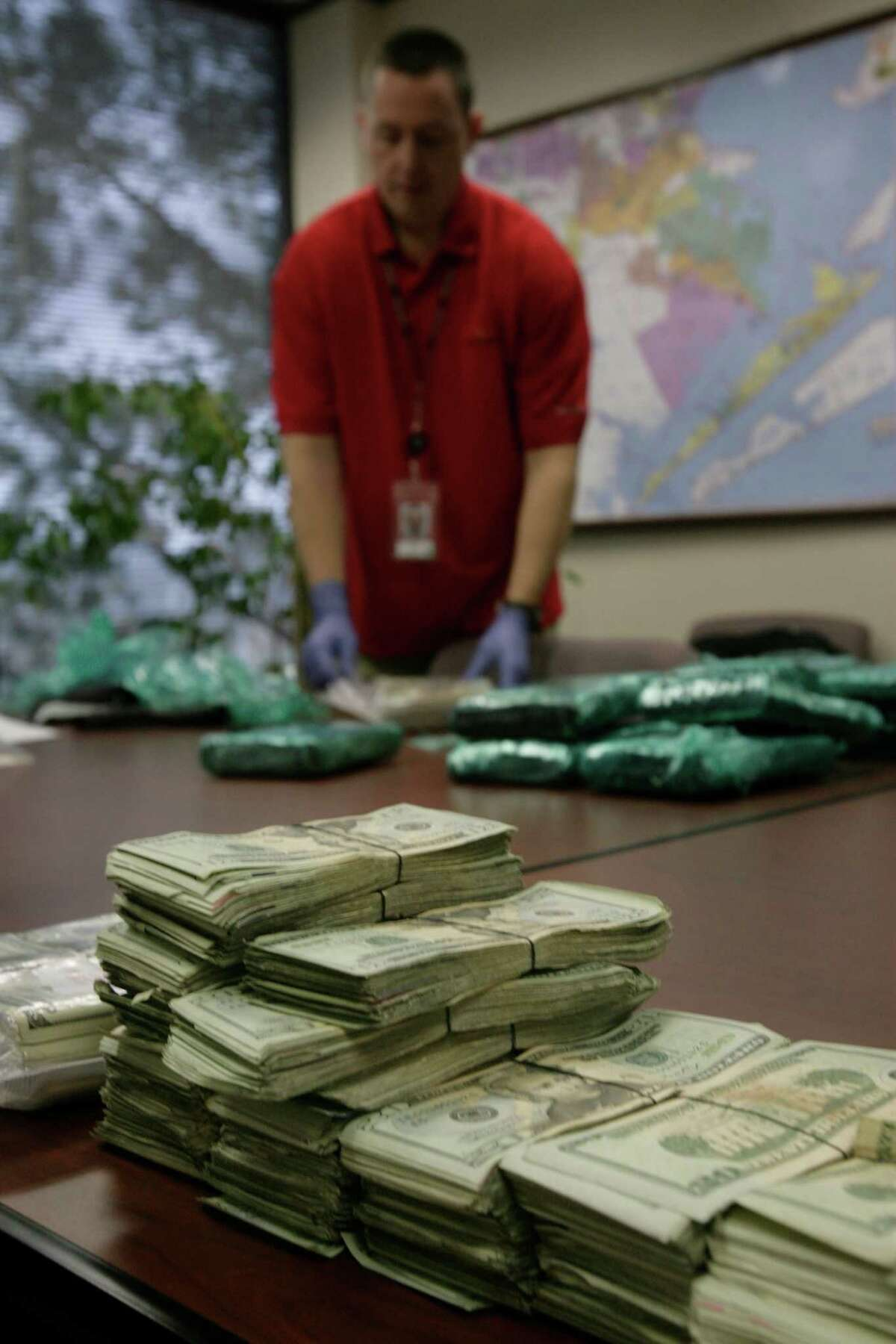 Drug Enforcement Administration agent Bill Furay cuts into packaged money at a DEA facility Wednesday February 23, 2011. Agents confiscated the money after a sting operation in Alabama. The estimated $1 million was part of a network in which cocaine was pumped from South Texas to Alabama.