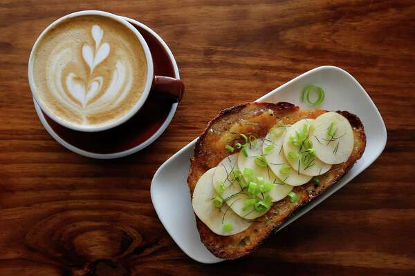 The Fairview Coffee Bar and Grub offers customers their seasonal house-baked sourdough bread toasted and prepared with sharp cheddar, Hot Apple Pie jam, honey crisp apple slices, fennel and green onion served with alongside a cup of cappuccino.