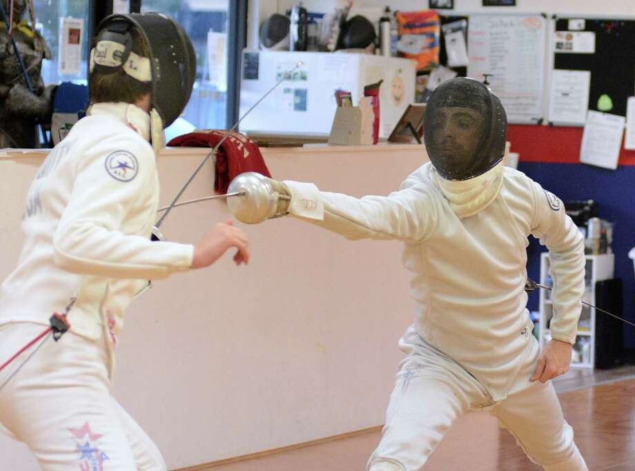 Fourteen year old William Smith, The Woodlands High School ninth grader, and fifteen year old Wolfe Crouse, of Willis, practice their fencing during a practice session at Alliance Fencing Academy, 27326 Robinson Road in Oak Ridge North. Photo: David Hopper, Freelance / freelance