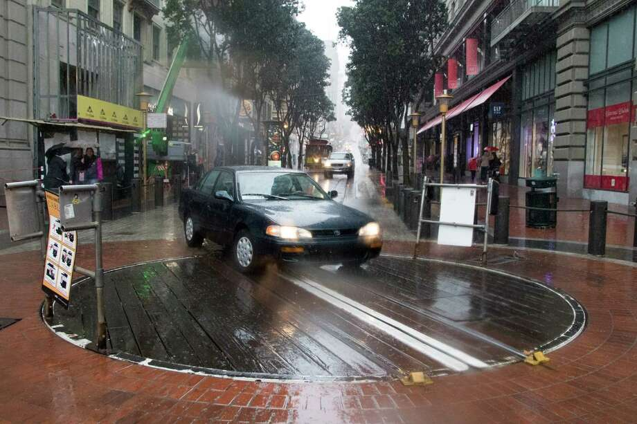 A car drove around a cable car and onto the Powell Street turnaround platform during the rainstorm in San Francisco on Thursday, Dec. 3, 2015. Photo: SF Gate / Douglas Zimmerman