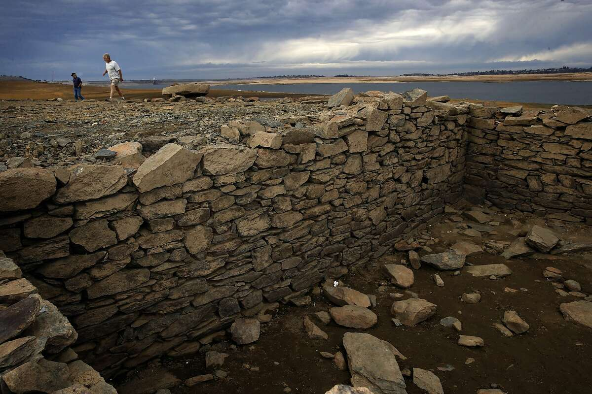 Stan Hronik, (left) and Stan Schmalz explore the remnants of the gold rush town of Red Bank, Calif., including what is believed to be a basement, which is now visible with the low water levels at Folsom Lake, seen on Thurs. December 3, 2015, in Folsom, Calif.