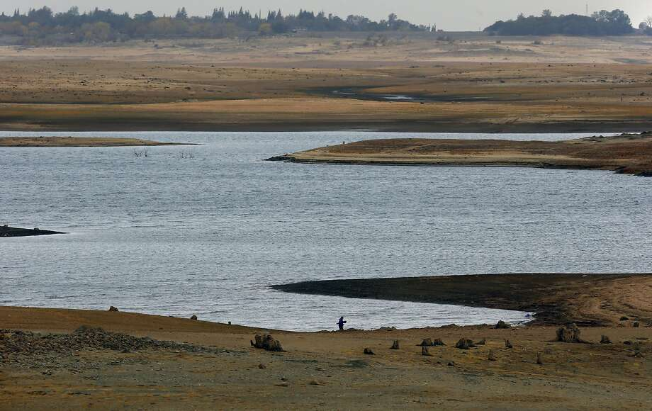 John Frakes walks his dog along Folsom Lake in December, where water levels have been recovering with the recent wet weather but still remain low. Photo: Michael Macor, The Chronicle