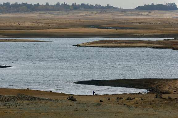 John Frakes walks his dog along the barren landscape the water levels dropping drastically at Folsom Lake as seen on Thurs. December 3, 2015, in Folsom, Calif.