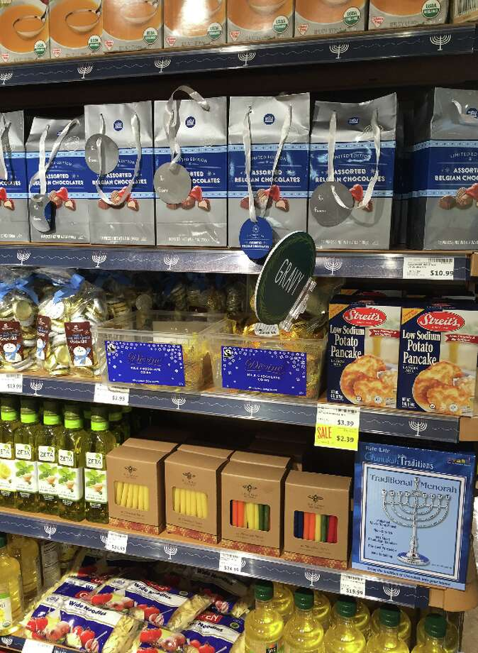 """When stores attempt to create Hanukkah sections, sometimes they just don't get it. These displays can feature everything from completely unrelated items to merchandise that could be offensive to those who are more religious.One example is this Hanukkah shelf at a Whole Foods in San Rafael. It has Hanukkah necessities, including a menorah, candles and lots and lots of oil (Hanukkah is about a miracle of oil and you cook delicious Hanukkah latkes in oil). Other items, such as a bunch of kosher salt and chicken broth (not pictured) are a bit of a stretch, but still Jewish. However, the assorted Belgian chocolates and the random """"gravy"""" marker? Not related. Photo: Jessica Mullins, SFGATE"""
