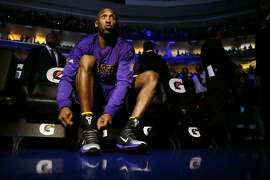 Los Angeles Lakers' Kobe Bryant laces up his shoes ahead of a basketball game against the Philadelphia 76ers Tuesday, Dec. 1, 2015, in Philadelphia. (AP Photo/Matt Rourke)