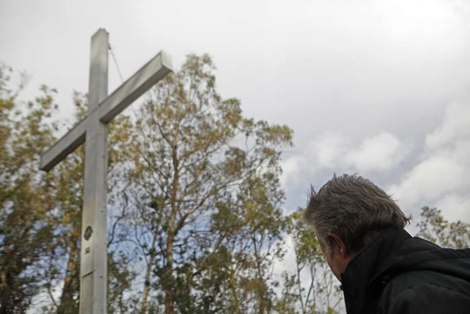 Larry Hicok of the  of East Bay Atheists Society, looks up at the source of contention, the cross  which is located Albany Hill Park, in Albany Calif. on December 3, 2015. It has foundation issues  and cracks at the base and is maintained by the Lions Club. There is also a electoral wire that is connected from the structure to a tree, which Hicok points out is  illegal. Photo: Franchon Smith, The Chronicle