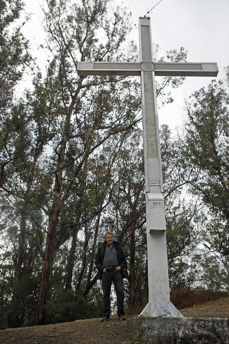 Larry Hicok of the  of East Bay Atheists Society, standing at the source of contention, the cross  which is located Albany Hill Park, in Albany Calif. on December 3, 2015. It has foundation issues  and cracks at the base and is maintained by the Lions Club. There is also a electoral wire that is connected from the structure to a tree, which Hicok points out is  illegal. Photo: Franchon Smith, The Chronicle