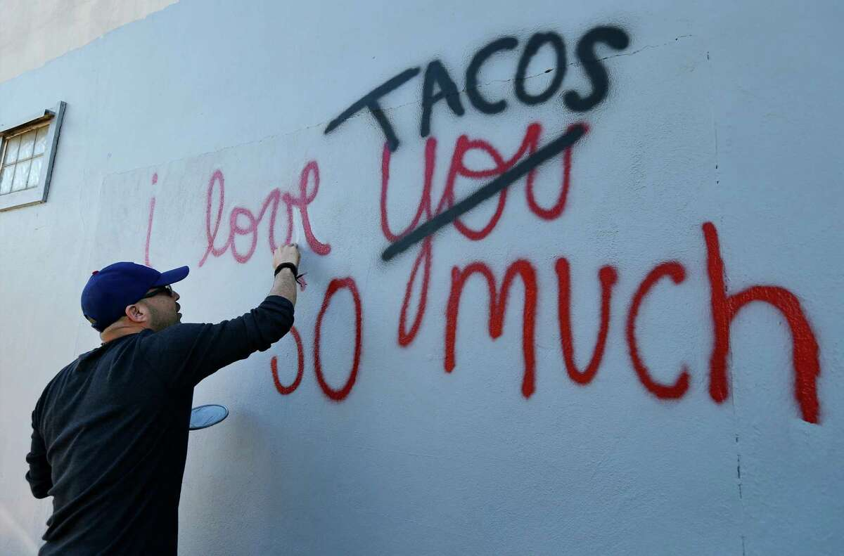 """Luis Munoz touches up his artwork """"I love tacos so much"""" which gained social media attraction earlier in the week after it was accidentally painted over by the city on Thursday, Dec. 3, 2015. After city employees were informed of their mistake, they supplied Munoz with paint and he went back to the now gray wall to remake his ode to the city and to tacos. Dozens of people who were informed of the incident via social media turned out to show their support as he re-created his art on the wall. Munoz created the artwork partly as an homage to a mural he saw in Austin and partly due to his love for tacos and the city. When social media took notice, Munoz decided to dedicate his artwork to charity whenever someone reposted his work. He was relieved to re-create his work of art but was also saddened that his original was no longer visible. However, his new homage still garnered attention from social media as well as by-passers who stopped for photos."""