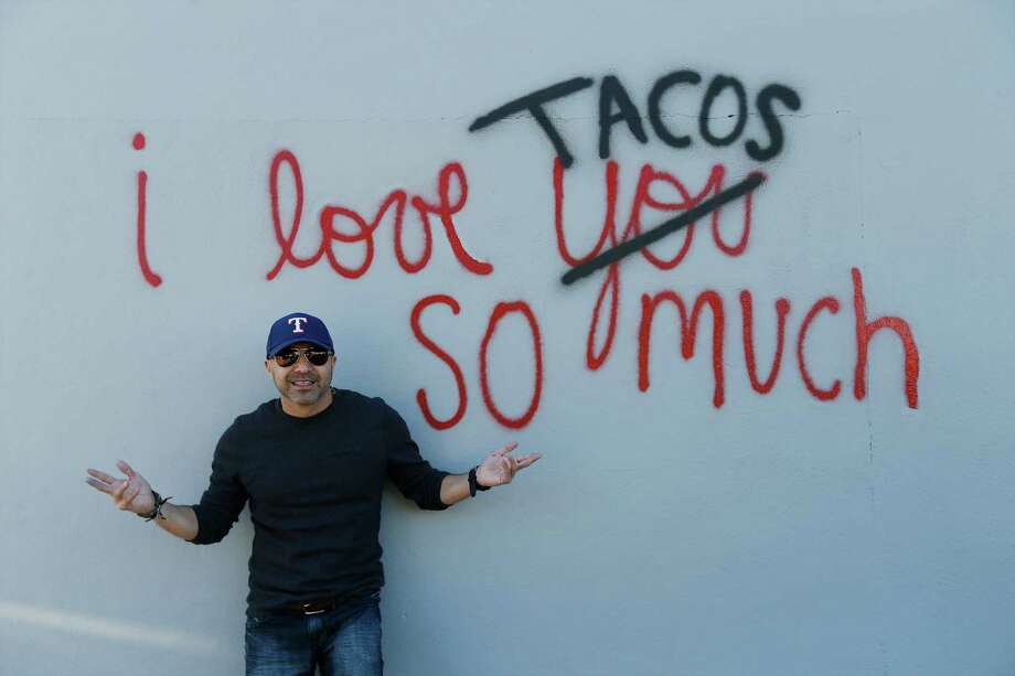 "Luis Munoz poses with his re-created work of art, ""I love tacos so much,"" which had gained social media attraction earlier in the week after it was accidentally painted over by the city on Thursday, Dec. 3, 2015. After city employees were informed of their mistake, they supplied Munoz with paint and he went back to the now gray wall to remake his ode to the city and to tacos. Dozens of people who were informed of the incident via social media turned out to show their support as he re-created his art on the wall. Munoz created the artwork partly as an homage to a mural he saw in Austin and partly due to his love for tacos and the city. When social media took notice, Munoz decided to dedicate his artwork to charity whenever someone reposted his work. He was relieved to re-create his work of art but was also saddened that his original was no longer visible. However, his new homage still garnered attention from social media as well as by-passers who stopped for photos. Photo: Kin Man Hui, San Antonio Express-News / ©2015 San Antonio Express-News"
