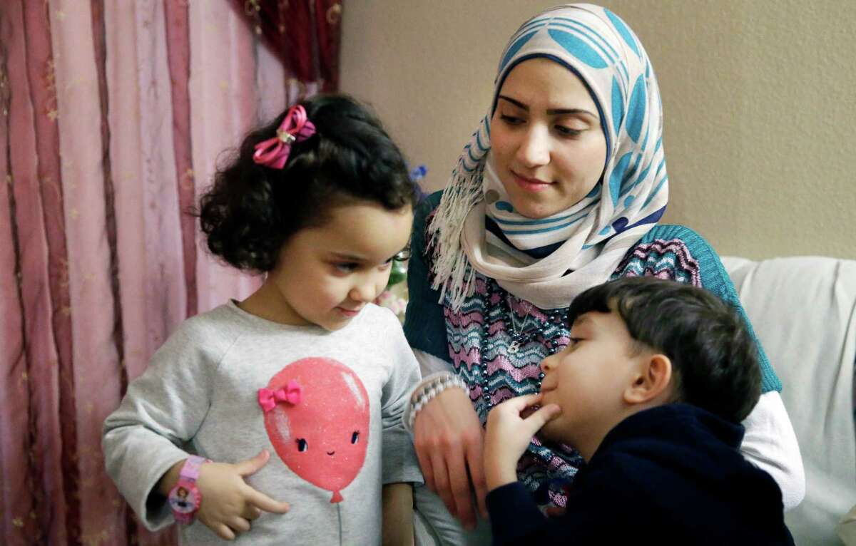 In this photo made Monday, Nov. 29, 2015, Syrian refugee Maryam al Jaddou, center, looks on as her children twins Maria, left, and Hasan, sit with her at their apartment in Dallas. The 30-year-old al Bashar al Jaddou decided to leave Syria in 2012 after his family?'s home in Homs was bombed and there was nowhere safe left to live. (AP Photo/LM Otero)