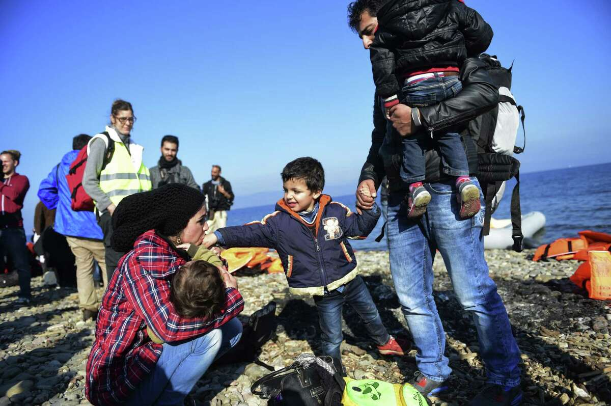 A Syrian family cheers after arriving on the Greek island of Lesbos after crossing the Aegean Sea from Turkey with other refugees and migrants on November 19, 2015. European leaders tried to focus on joint action with Africa to tackle the migration crisis, as Slovenia became the latest EU member to act on its own by barricading its border. AFP PHOTO/BULENT KILICBULENT KILIC/AFP/Getty Images