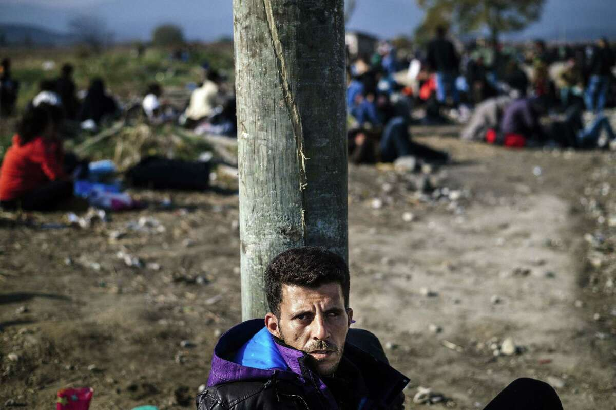TOPSHOTS A Syrian man from Daraa waits to enter a registration camp along with other migrants and refugees after crossing the Greek-Macedonian border near Gevgelija on November 18, 2015. More than 800,000 refugees and migrants have landed in Europe so far this year and more than 3,000 have died while crossing the Mediterranean in search of a new life in the world's largest economy. AFP PHOTO / DIMITAR DILKOFFDIMITAR DILKOFF/AFP/Getty Images