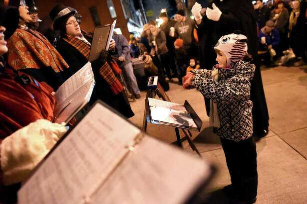 Georgia Diem, 7, of Saratoga Springs, right, stands in as guest conductor as she leads St. Paul's Lutheran Church choir in a Christmas carol during the 29th annual Victorian Streetwalk on Thursday, Dec. 3, 2015, in Saratoga Springs, N.Y. The event featured music acts, choral groups, face painting, seasonal treats and Santa Claus. (Cindy Schultz / Times Union)