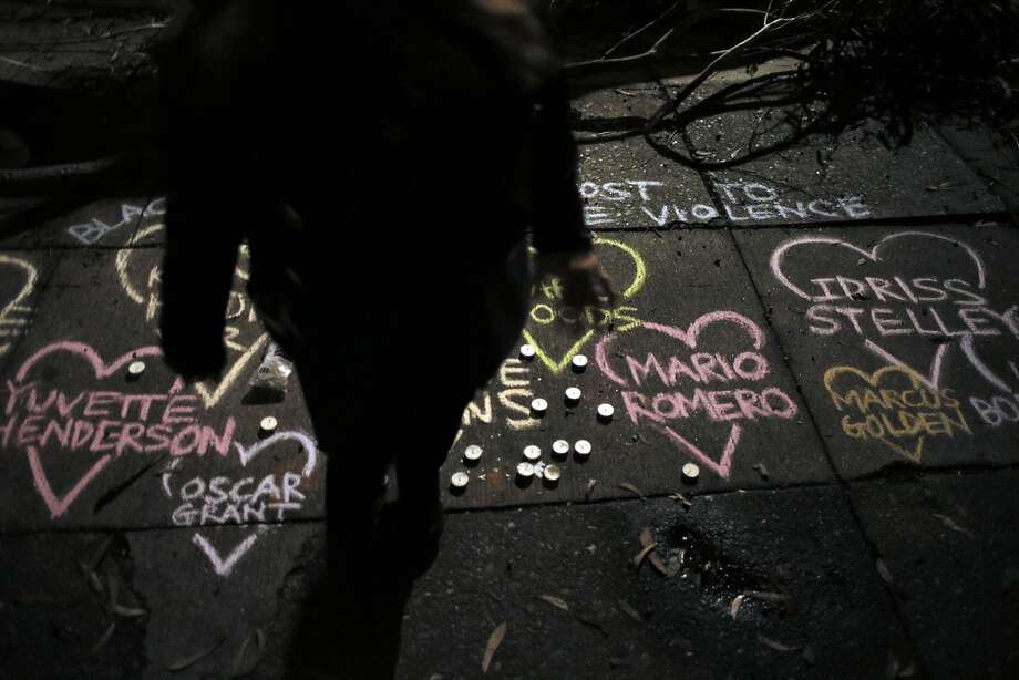 A member of the community stands near chalk art showing the names of those killed by police at the site where Mario Woods was shot and killed by San Francisco Police to commemorate the young man in the Bayview district of San Francisco, Calif., on Thursday, December 3, 2015. Photo: Carlos Avila Gonzalez, The Chronicle