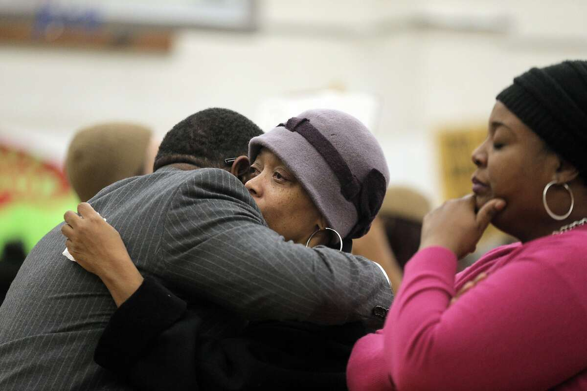 Gwen Woods, mother of Mario Woods is hugged by attorney Adante Pointer as community members gathered St. Paul of the Shipwreck for a community meeting after Woods was shot and killed by San Francisco Police in the Bayview district of San Francisco, Calif., on Thursday, December 3, 2015.