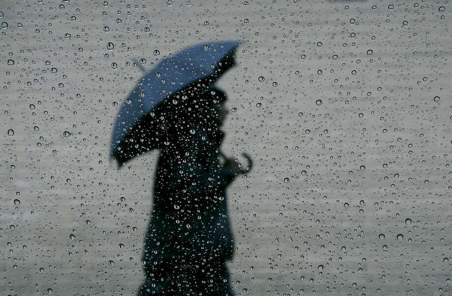 A man carries an umbrella as he walks down Larkin Street in San Francisco on Dec. 3. A wet-weather front set to arrive Friday evening is expected to kick off series of rainy days through Christmas.Since Bay Area residents often freak out about the rain, scroll through the slideshow to see what we are all guilty of when that strange stuff falls from the sky. Photo: Jeff Chiu, Associated Press