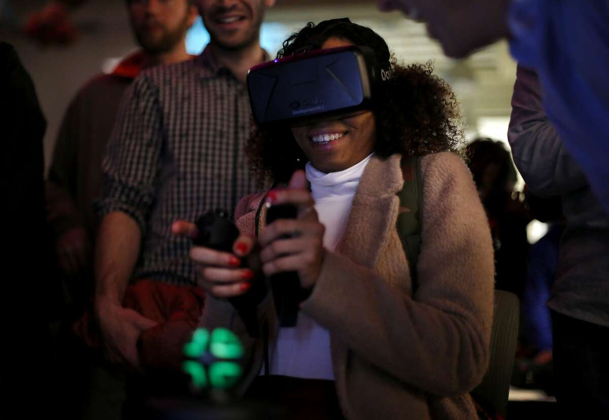 Selena Davant maneuvers around a digital world using an Oculus Rift headset and hand-held controllers at the virtual reality conference Off Planet VR in Berkeley, California, on Thursday, Dec. 3, 2015.