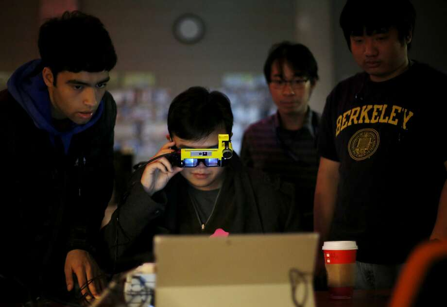 Ali Tan (center) uses an augmented reality headset while Rohan Murthy (left), Hung Vu and Eric Nguyen from Virtuality Reality at Berkeley look on at the virtual reality conference Off Planet VR in Berkeley, California, on Thursday, Dec. 3, 2015. Photo: Connor Radnovich, The Chronicle