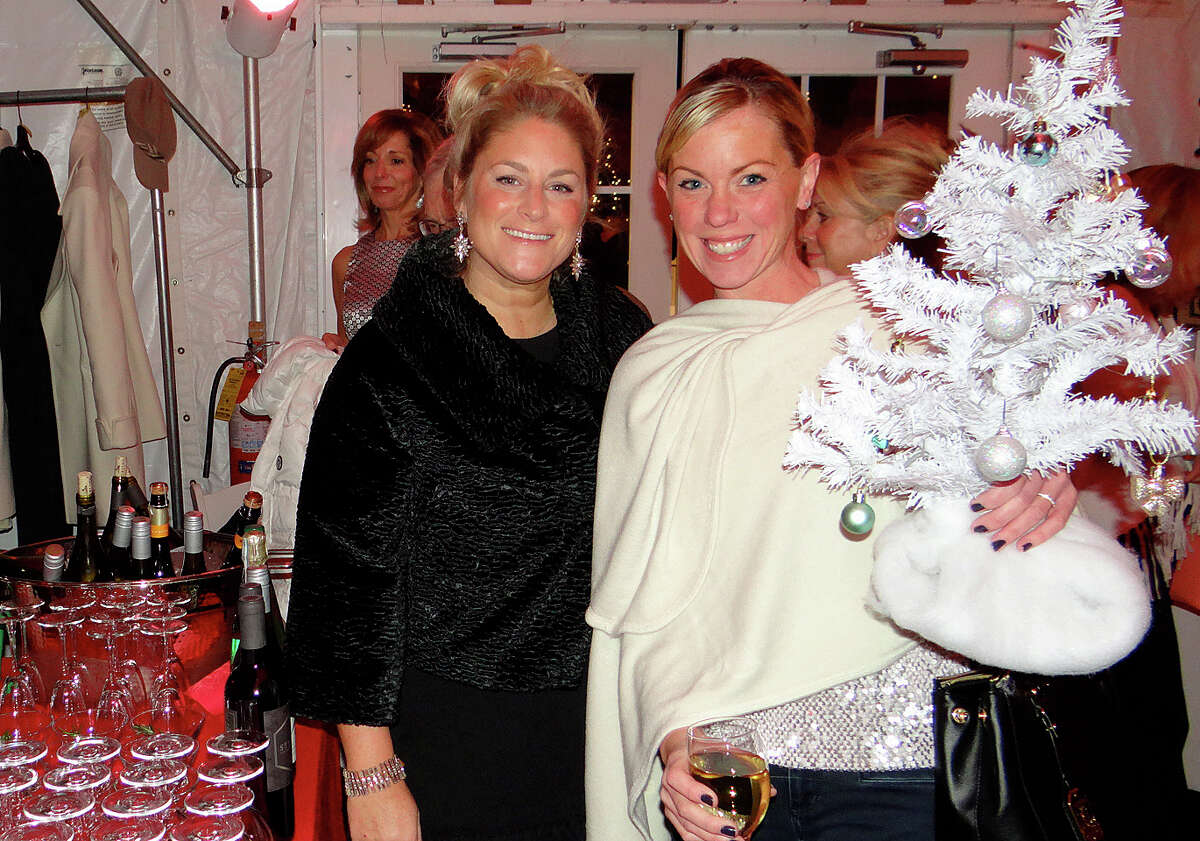 Fairfielders Amy Scarella and Bridget Lesizza tote a table topper tree at the Fairfield Christmas Tree Festival's opening night preview party at the Burr Homestead.