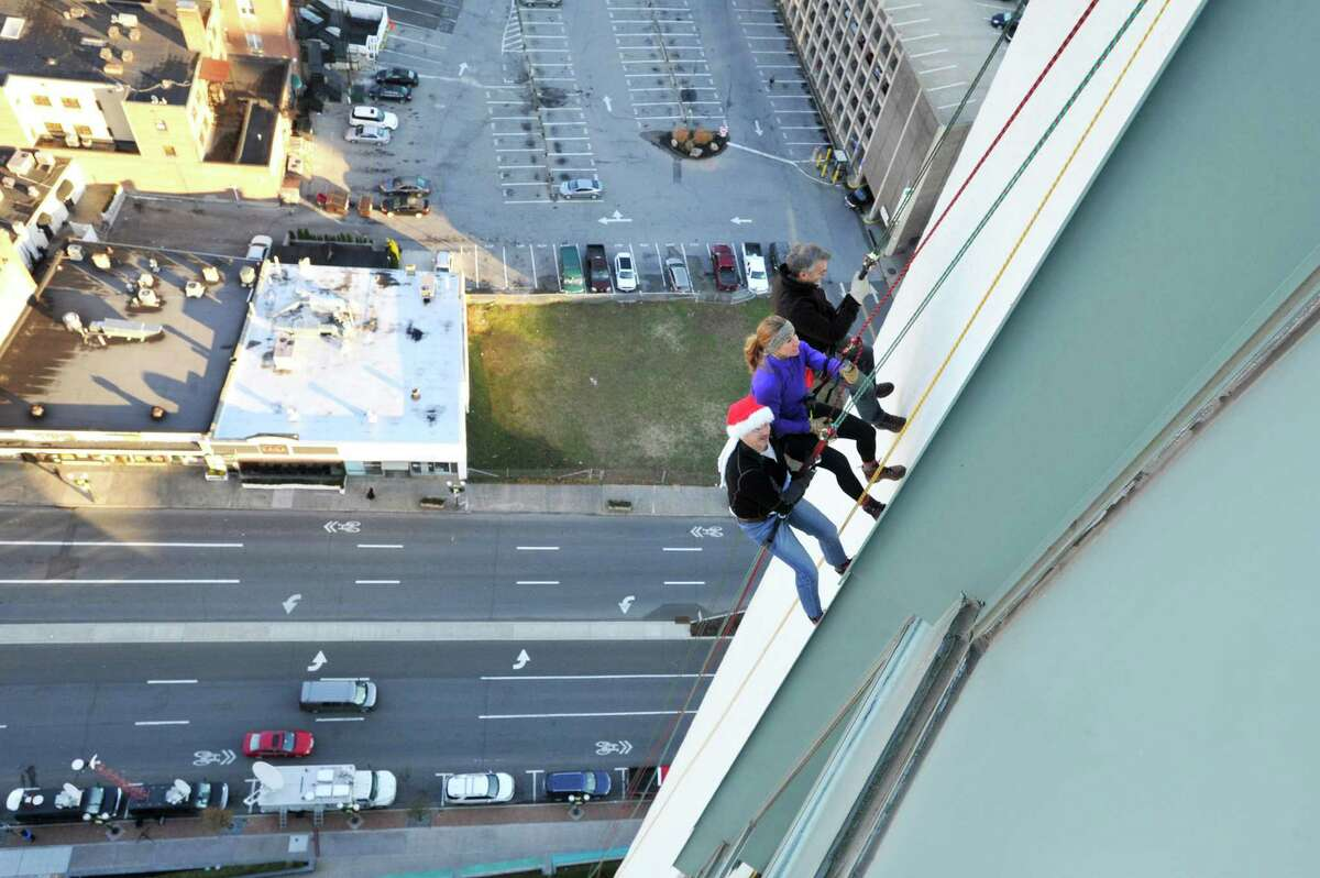 From left, New York Yankees General Manager Brian Cashman, Yogi Berra's Lindsay Berra and New York climber Brian Van Orsdel rappel down the Landmark Building in downtown Stamford on Friday morning, Dec. 4, during a practice run for Sunday's Heights & Lights event.