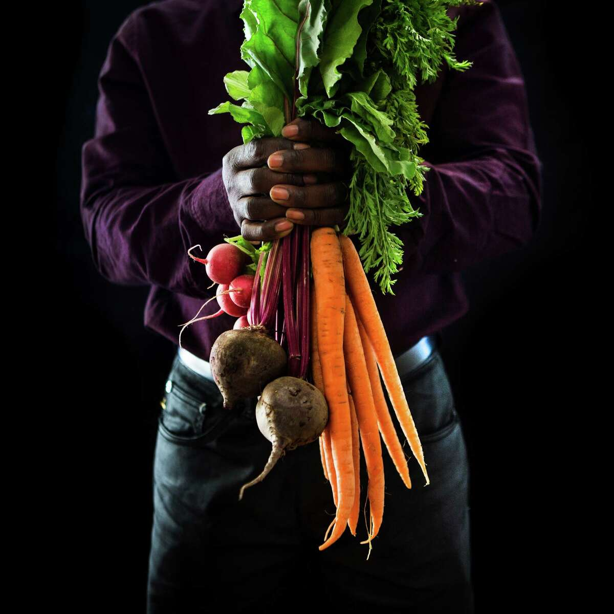 Adrien Ikaba, original from Congo holds vegetables. Ikaba was trained in economy but became a farmer when he migrated to the United States. Wednesday, Oct. 14, 2015, in Houston.